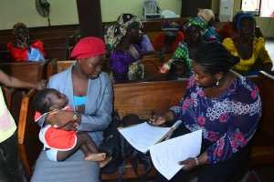Sesor Trustee, Sewuese Okubanjo talks to a mother about enrolling her children in school