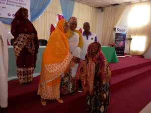 Dr Zainab Gimba presenting an envelope to a beneficiary